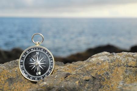 Orientation Concept - Analogic Compass Abandoned on the Rocks Stock Photo