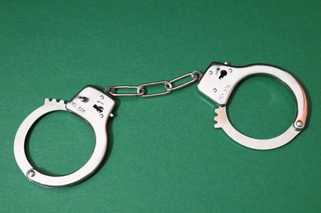 handcuffing: One Pair of Handcuffs on a Colored Background