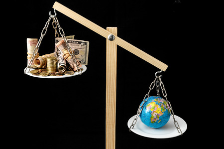 Globe Planet Earth and Money on a Two Pan Balance Stock Photo