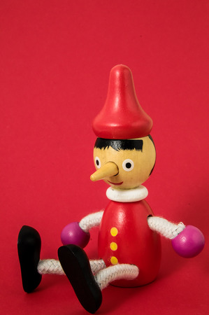 Pinocchio Toy Standbeeld op een gekleurde achtergrond Stockfoto