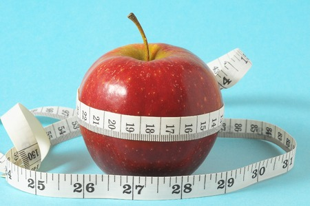 Measuring Tape Wrapped Around Red Apple as a Symbol of Diet photo