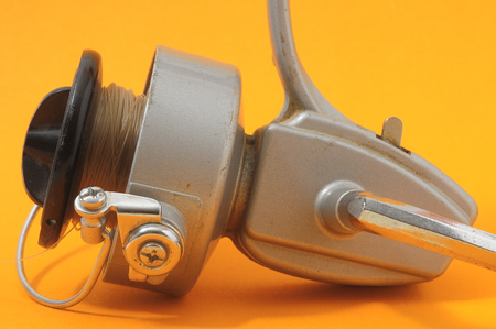 One Vintage Old Fishing Reel on a Colored Background Stock Photo - 26104474