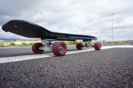 80 s: Vintage Style Longboard Black Skateboard on an Empty Asphalt Desert Road