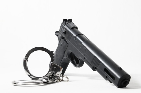 Weapon Crime Concept Gun and Handcuffs on a White  photo
