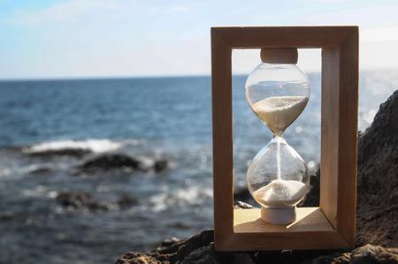arena blanca: Concepto de tiempo de reloj de arena blanca de la arena en las rocas volc�nicas Foto de archivo