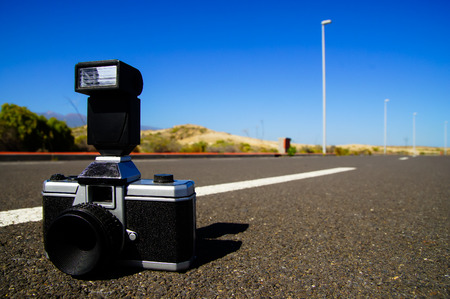 Street Photography Concept Vintage Camera on the Asphalt photo