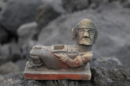 Ancient Maya Statue on the Rocks near Ocean photo