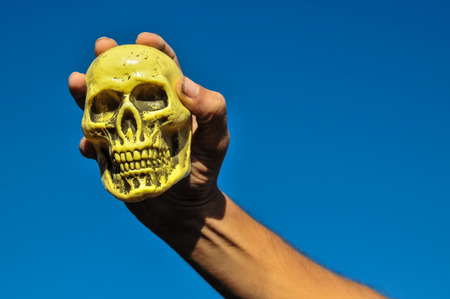 Vintage Old Skull and Human Hand over a Blue Sky photo