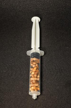 Medical Syringe Full of Pill Drugs on a Black Background photo