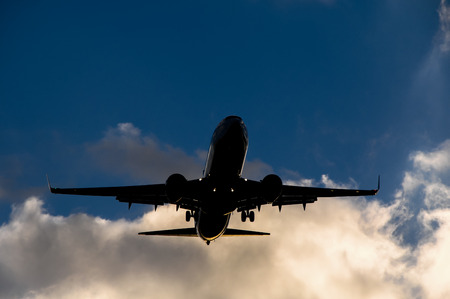 Silhouette of an Airplane Landing over a evening sky photo