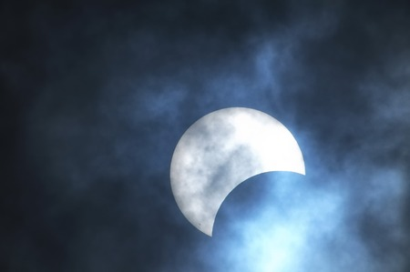 Partial Solar Eclipse on a Cloudy Day 03 11 2013 Stock Photo - 27203708
