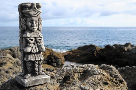 Ancient Maya Statue on the Rocks near Ocean photo