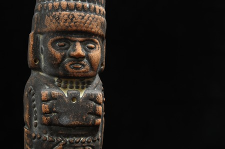 One Ancient Mayan Statue on a Black Background photo