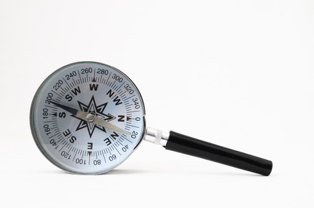 Orientation Concept - Analogic Compass and Loupe on a White Background Stock Photo
