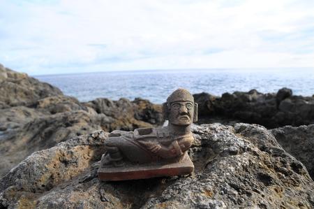 Ancient Maya Statue on the Rocks near the Ocean photo
