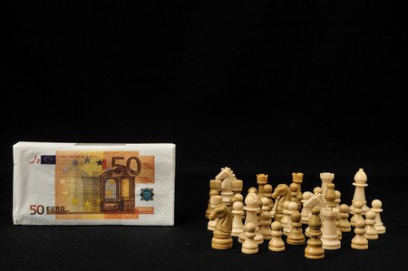 Money Strategy Concept White Chess and Currency on a Black Background photo