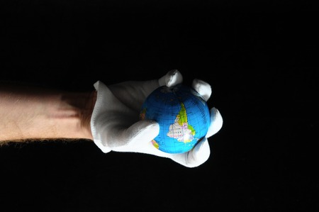 Planet Earth and a Hand on a Black Background photo