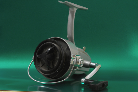One Vintage Old Fishing Reel on a Colored Background photo