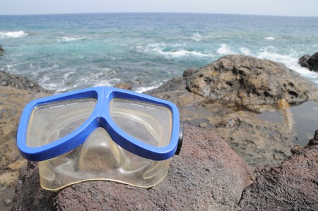 Blue Old Diving Mask on the Rocks near the Beach photo