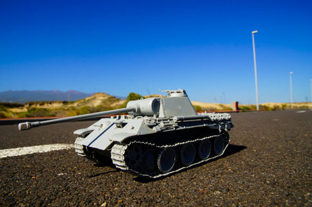 Modern War Concept Model Tank in the Middle of an Asphalt Road Stock Photo