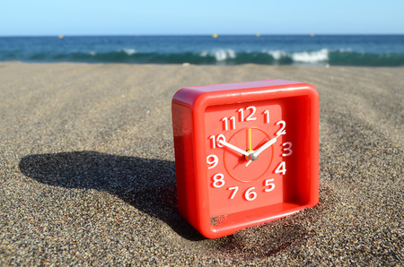 Classic Analog Clock In The Sand On The Beach Near The Ocean photo