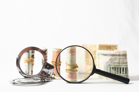 Tax Crime Concept Money and Handcuffs on a White Background Stock Photo