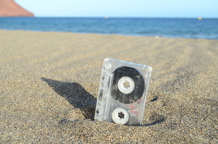 Ancient Retro Musicassette on the Sand near the Water photo