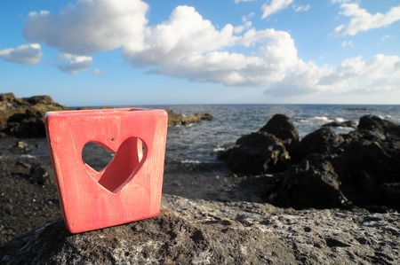 valentine s day beach: Red Heart Shaped Candle Holder Near the Ocean Stock Photo