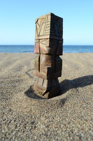Ancient Maya Statue on the Sand Beach near the Ocean photo