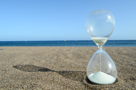 Een Zandloper op het zandstrand dichtbij de oceaan Time Concept Stockfoto