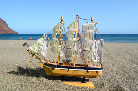 Sail Ship Toy Model in the Beach Sand Close-up photo