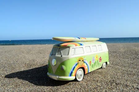 Detail of a Vintage Hippie Van Toy in the Beach with Surfboard on Roof photo