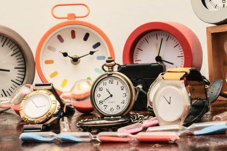 Many Different Clocks on a Woden Table photo