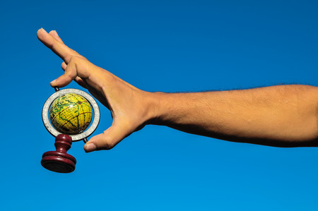 Vintage Old Globe Earth and Human Hand over a Blue Sky photo