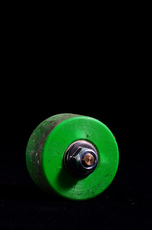 Old Vintage Consumed Skate Wheel on a Black Background photo