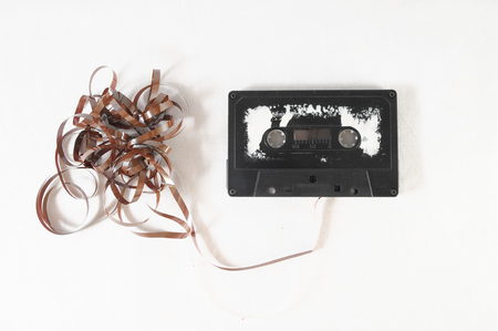 Ancient Vintage Used Musicassette over a White Background Stock Photo