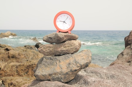 One Red Clock on the Rocks Near the Ocean photo