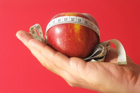 Diet Apple and Meter on the Hand on a Colored Background photo