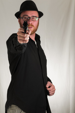 Black Dressed Young Man Holding a Pistol Gun photo