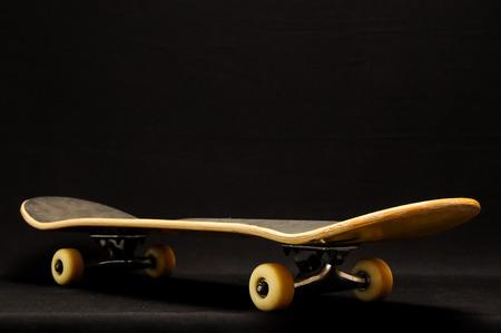 80 s: Vintage Style Black Skateboard on a black Background