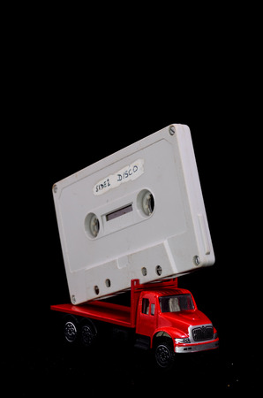 Music Concept Red Truck and Audio Music Tape on a Black Background photo