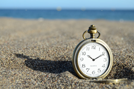 Classic Analog Clock In The Sand On The Beach Near The Ocean Stockfoto