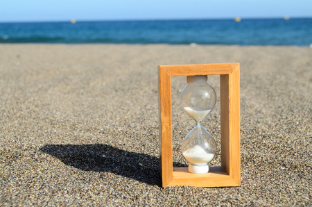 One Hourglass on the Sand Beach Near the Ocean Time Concept photo