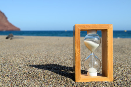 One Hourglass on the Sand Beach Near the Ocean Time Concept Archivio Fotografico
