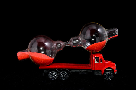Time Transportation Concept Hourglass Watch on a Red Toy Truck over Black  photo