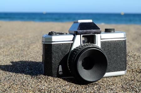 Old Photo Camera on the Sand Beach photo