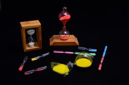 Deadline Concept Broken Hourglass with Yellow Sand on Black