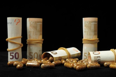 Some Pills And Money on a Black Background photo