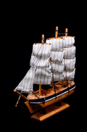 Ship Sailboat Wooden Model Figurine on a Black Background photo