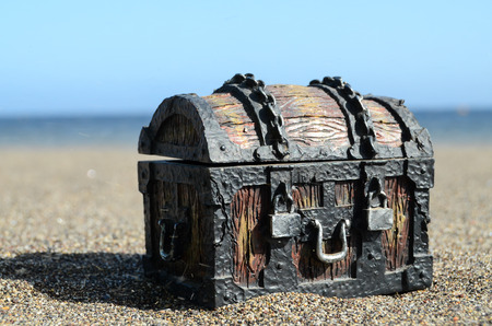 bury: Old Classic Wood and Iron Treasure Chest on the Beach